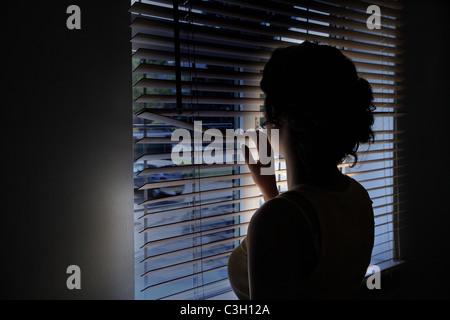Mujer mirando aunque la persiana de una ventana en una oscura calle vacía.