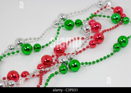 Blanco verde rojo bolitas de plástico brillante sobre un fondo blanco.