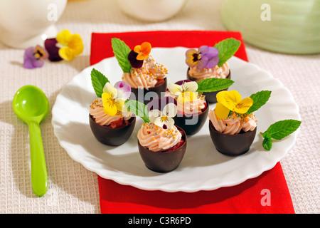 Tazas de chocolate con nata y flores. Receta disponibles.