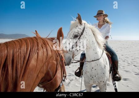 2 personas a caballo en la playa