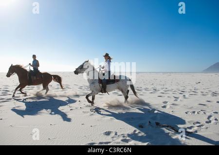 2 personas a caballo en la arena
