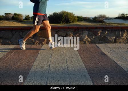 Macho joven atleta trotar en el paseo marítimo. Piernas en movimiento. Una tranquila Playa con dunas de arena en el fondo