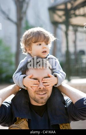 Padre de un hijo pequeño llevando sobre sus hombros, hijo del padre que cubre los ojos con sus manos