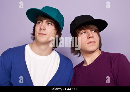 Dos muchachos adolescentes luciendo gorras de béisbol apartar la mirada, Foto de estudio Foto de stock
