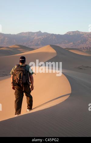 Hombre caminando sobre las dunas de arena de mezquite, el Parque Nacional Valle de la Muerte, California