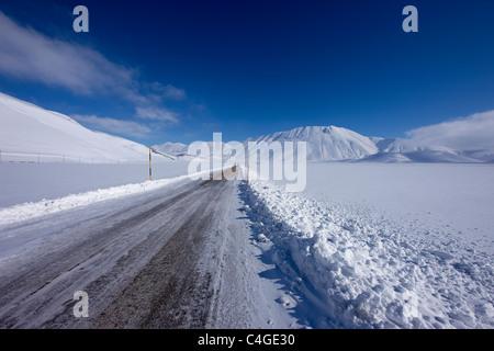 La carretera en todo el Piano Grande en invierno, el Parque Nacional de Monti Sibillini, Umbría.