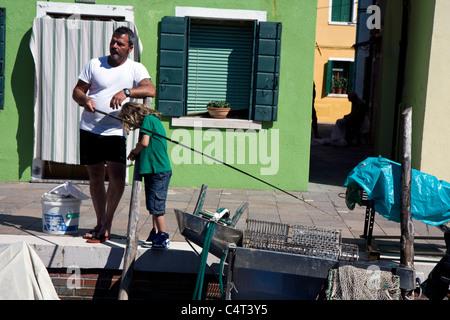El hombre y el niño la pesca en un canal en la ciudad de Burano en Italia, junto a Venecia