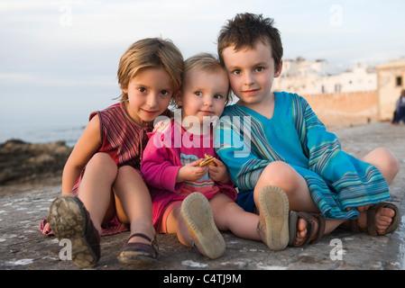 Hermanos jóvenes sentados juntos en la playa rocosa, Retrato
