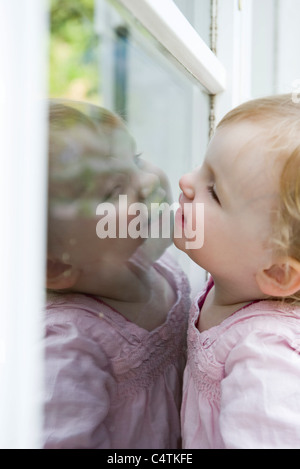 Niño Niña mirando a través de la ventana