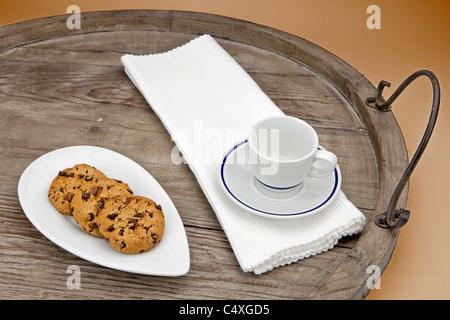 Las galletas con trocitos de chocolate servido en una bandeja de madera antiguos