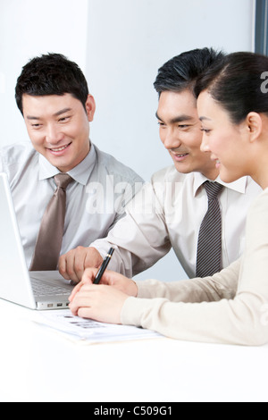 Ejecutivos de negocios, mostrando los jóvenes empresarios algo en el equipo