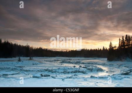 Un Fish Creek cubiertas de hielo refleja el cielo de la tarde cerca del Tony Knowles Coastal Trail y Westchester Laguna, Alaska, Invierno