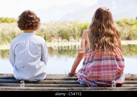 Vista trasera de hermanos sentados juntos en un muelle