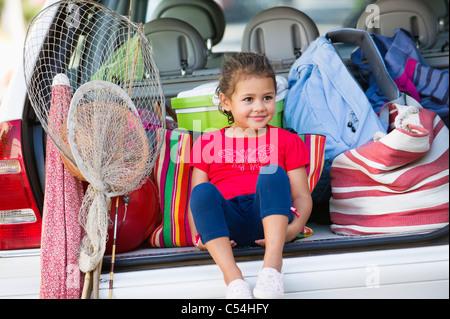 Cute Little Girl sentado en el maletero del coche