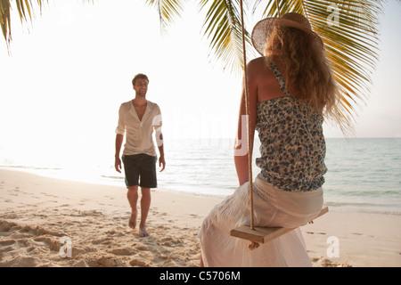 Mujer en swing con novio en la playa Foto de stock