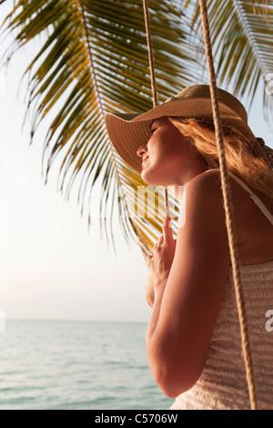 Mujer sentada sobre swing en playa Foto de stock