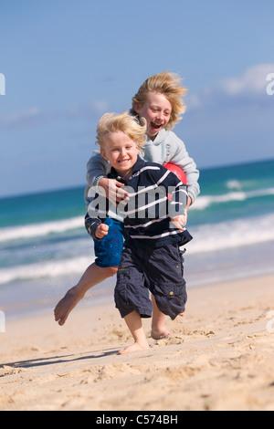 Muchachos jugando con bolas rojas en la playa