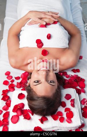 Hermosa mujer sonriente tumbado sobre una camilla de masaje con pétalos de rosa alrededor