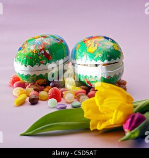 Close-up de dos huevos de Pascua con caramelos y tulipanes contra el fondo de color rosa Foto de stock