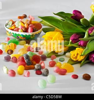Close-up de tulipanes y dulces de pascua en superficie gris Foto de stock