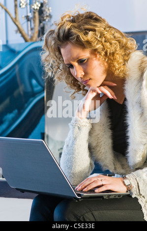 Chaqueta de piel joven trabajando en un portátil.