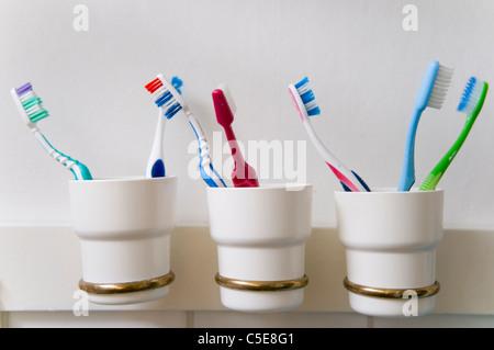 Close-up de cepillos de dientes en tres soportes en fila contra la pared en el cuarto de baño
