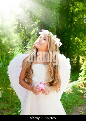 Los niños ángel chica en bosque con flores en la mano mirando el cielo haces de luz