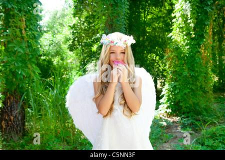 Los niños ángel chica oliendo rosas de flor en el bosque con alas blancas y corona