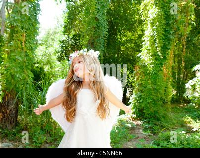 Los niños ángel chica brazos abiertos en bosque con alas blancas y corona de flores