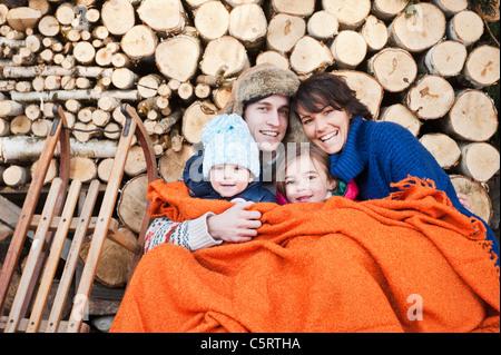 País Austria, Salzburgo, Flachau, Familia bajo manta de lana sentado delante de Leñas