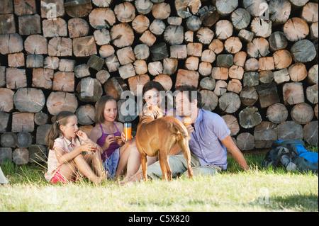 Italia, el Tirol del Sur, la familia tener un picnic en frente del montón de madera