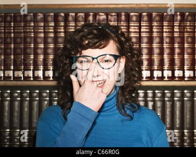 Mujer empujando hacia arriba las gafas en la biblioteca Foto de stock
