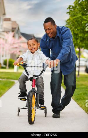 Padre enseñar al hijo a andar en bicicleta Foto de stock