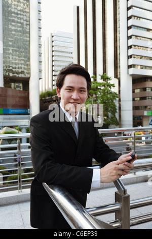 Empresario asiático la mensajería de texto del teléfono celular al aire libre