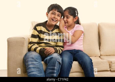 Chica susurrando en su oído hermanos Foto de stock