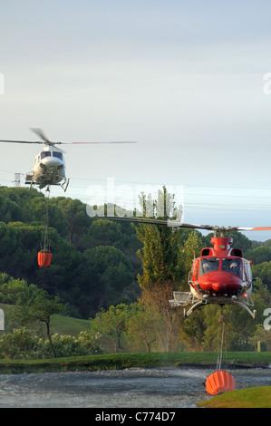 Helicóptero Bell 412 recogiendo agua, Cabopino Golf, Costa del Sol, Málaga, Andalucía, España, Europa Occidental.