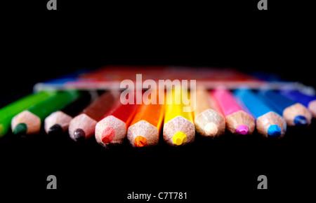 Fila de colores brillantes a través del lápiz negro en el enfoque superficial