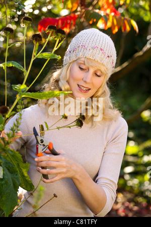 Mujer trabajando en el jardín de otoño