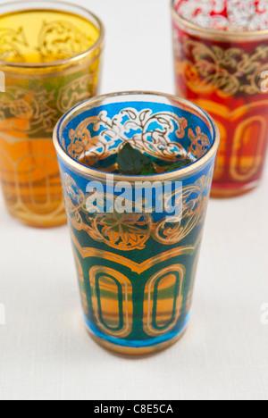 Pequeños vasos de té a la menta de color sobre un fondo blanco. Foto de stock