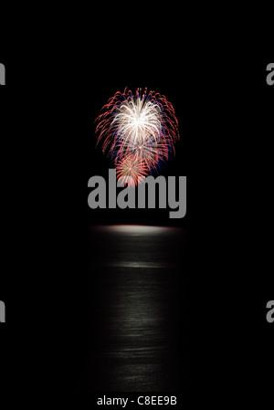 Rojo, blanco y azul de Fireworks con agua por debajo y fondo negro