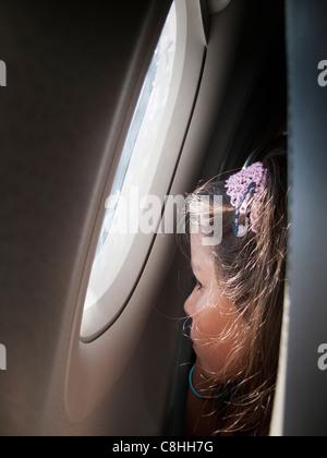 Niño mirando por la ventana en un avión