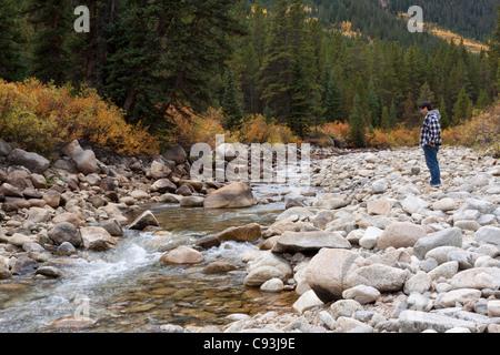 Hombre asiático de pie en Rocky River Bed disfrutando la naturaleza, viendo creek por flujo de agua en otoño en Colorado Foto de stock