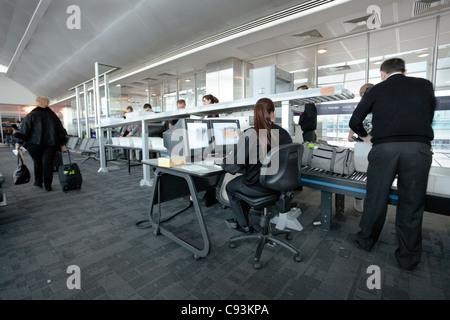 Personal de seguridad del aeropuerto los pasajeros equipaje en la puerta de salida en Estambul, Turquía, 22 de marzo de 2011.