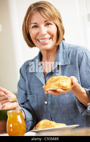 Mujer de mediana edad comer cruasanes Foto de stock