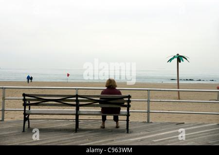 Una solitaria mujer sentada en un banco en el Broadwalk, Brighton Beach, Nueva York, Nueva York, Estados Unidos. (C) Marc Jackson