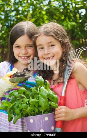 Alemania, Baviera, Hermanas haciendo jardinería en jardín, sonriendo, Retrato