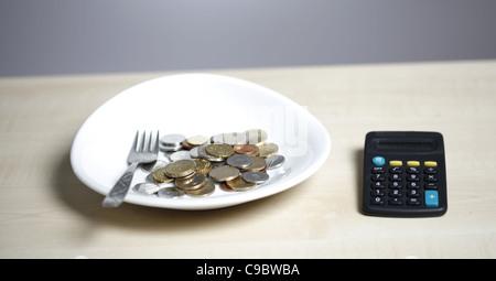 Muchas monedas en una placa blanca y una horquilla
