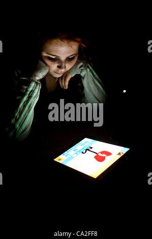 El 25 de marzo de 2012: una niña de 13 años utilizando la app dibujar algo sobre un nuevo Apple iPad 3 Tablet PC. Un pequeño OMGPOP, juegos basados en Nueva York empresa acaba de ser comprada por $180m (£113m) después de lanzar la app que fue descargado 35 millones de veces en las últimas seis semanas.