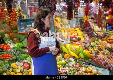 Mujer vendiendo frutas y hortalizas frescas en el puesto en el mercado de la Boqueria de Barcelona, España