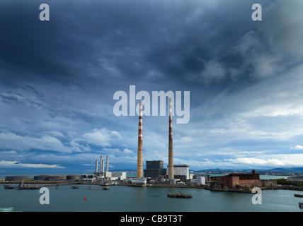 Por la noche en el río Liffey, mirando al sur de la ciudad de Dublín, a través de las dos chimeneas de Poolbeg Power Foto de stock